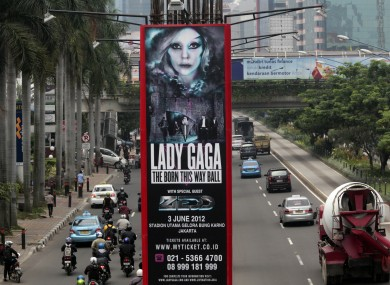 Motorists ride past a promotional banner for US singer Lady Gaga's Born This Way Ball Asia Tour in Jakarta, Indonesia