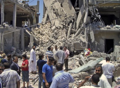 Members of the media and others examine the remains of a damaged residential building in Tripoli last June
