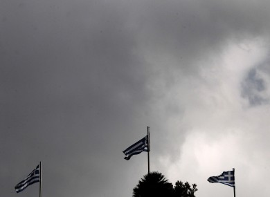 Greek flags wave at the roof garden of an hotel opposite to the Greek Parliament today