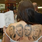 Westlife members signing the tattooed back of their fan Viki Jones at Easons, O'Connell St, Dublin. Photo: Sasko Lazarov/Photocall Ireland