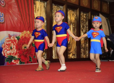 Chinese children wearing bathing suit walk on runway during a celebration for Children's Day