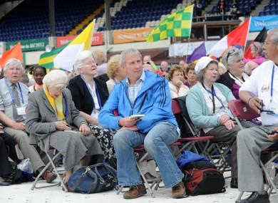 Pilgrims watch the opening address yesterday