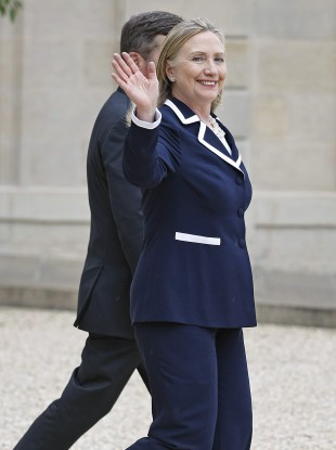 US Secretary of State Hillary Rodham Clinton waves a good bye as she leaves the Elysee Palace