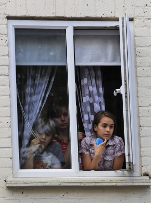 Children watch from their window during riots in Hackney, east London.