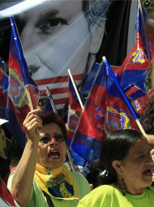 Demonstrators shout slogans as they hold up flags of the city of Quito in front of a Julian Assange poster during yesterday's march.