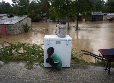 A young Haitian boy uses an appliance to shield himself from the storm in Port-au-Prince yesterday.