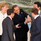 Silvio Berlusconi grasps the arm of Japanese PM Taro Aso and laughs at his cufflinks as world leaders look on helplessly. (Oli Scarff/PA Wire)