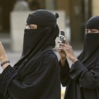 Saudi women use their mobiles to take pictures outside the Imam Turki bin Abdullah mosque as Saudis and residents perform Eid al-Fitr morning prayers in Riyadh. (AP Photo/Hassan Ammar/PA)