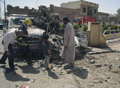 Citizens and security forces inspect the scene of a car bomb attack in Kirkuk, 290 kilometers (180 miles) north of Baghdad, Iraq