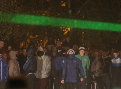 Masked people gathering at the scene of disorder on Sunday night