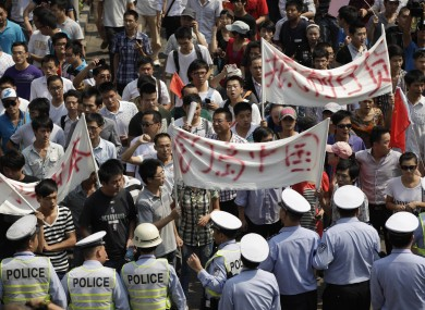 Police officers stop anti-Japan protesters marching through street in Shanghai, China.