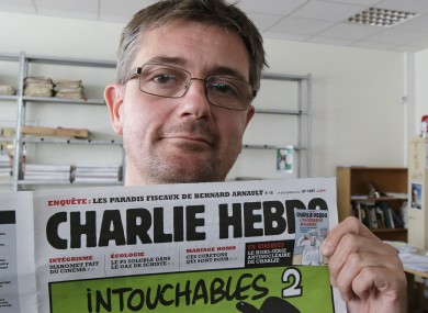 Publishing director of the satiric weekly Charlie Hebdo, Charb, displays the front page of the newspaper as he poses for photographers in Paris