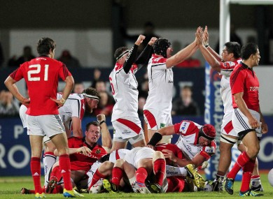 Conor Murray (Munster) reflects on his side's defeat as Stephen Ferris (Ulster) celebrates.
