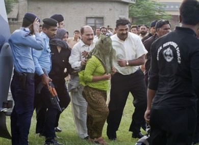 The young girl is escorted by police official to a helicopter following her release.