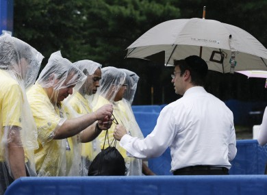 Security checks the bag of a tennis fan arriving during a rain delay in the fourth round of play.