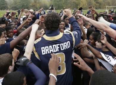 St. Louis Rams quarterback Sam Bradford reacts with school children as he takes part in a NFL organised coaching session for some London schoolchildren in Regents Park.