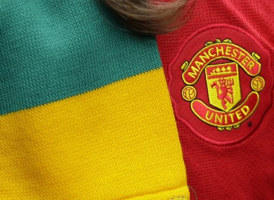 A Manchester United supporter is seen with a scarf in the colours of the anti-Glazer movement.