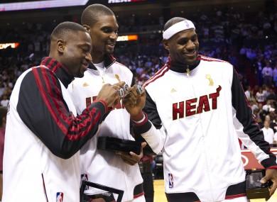 Dwayne Wade, Chris Bosh and LeBron James with their NBA championship rings.