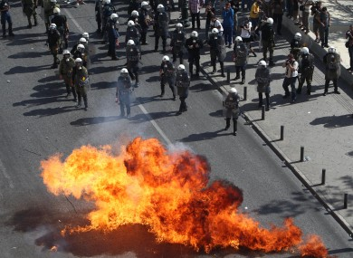 Protesters throw petrol bombs against riot police during a 24-hour nationwide general strike in Athens.