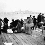 Immigrants stand outside at Ellis Island, looking torwards Manhattan and New York Bay, while they wait to be transferred and become residents of the United States on 30 October, 1912. (Corbis/Polfoto/Press Association Images)