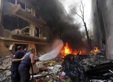 Lebanese firefighters extinguish burning cars at the scene of an explosion in the mostly Christian neighborhood of Achrafiyeh, Beirut.