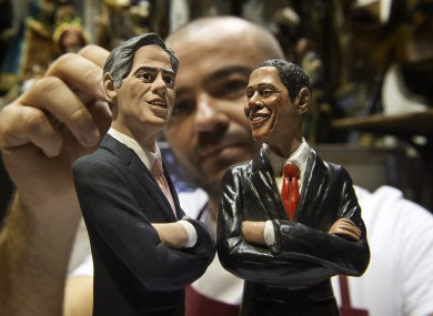 Italian Nativity scenes designer Genny Di Virgilio puts the final touches on two statuettes depicting President Barack Obama, right, and Republican rival Mitt Romney in his shop in Naples, Italy,