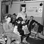 An MP stands among Japanese families en route to Ellis Island on a harbour boat after they arrived in New York, 11 August, 1945, on the SS Santa Rosa from Europe. They were slated for internment as 'enemy aliens'. (AP Photo/Matty Zimmerman)