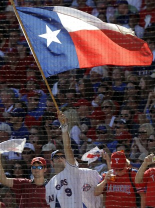 A fan of the Texas Rangers baseball team waves the state flag.