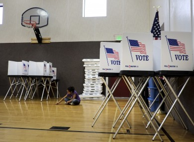 Jaylynn Notafraid, 9, sits amid voting booths in the gym at Crow Elementary School in Crow Agency in Montana.