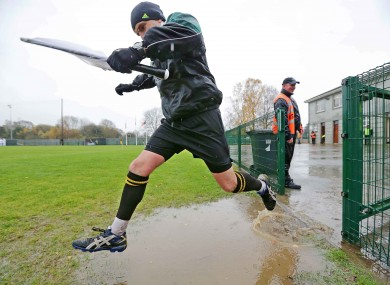 Linesman Diarmuid Kirwan clears a puddle on his way back out for the second half of the Dr Crokes game.
