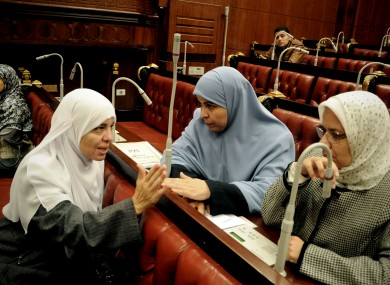 Azza el-Gharf of the Muslim Brotherhood's Freedom and Justice Party, second left, speaks with other members of the assembly during the vote last night