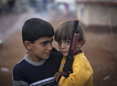 Two Syrian boys who fled with their families from the violence in their village, look on as one holds a gun toy at a displaced camp, in the Syrian village of Atmeh, near the Turkish border with Syria.