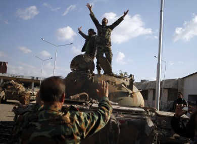 Syrian fighters celebrate the victory on top of a tank they took after storming a military base in Aleppo.