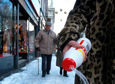 A woman fights the icy footpaths with salt in central Dublin in December 2010.