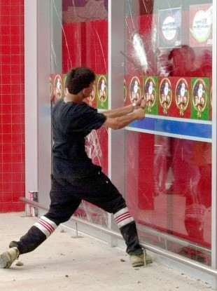 A man tries to break the windows of a supermarket in Buenos Aires earlier this week.