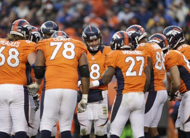 The Denver Broncos offense huddles around quarterback Peyton Manning.