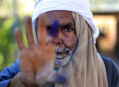 An Egyptian elderly man shows his inked finger after casting his vote on the second round of a referendum on a disputed constitution drafted by Islamist supporters of President Mohammed Morsi in Fayoum