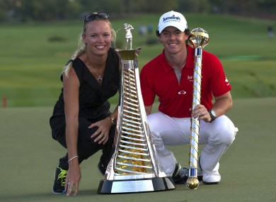 Rory McIlroy of Northern Ireland, right, holds the trophy with his girlfriend and Tennis player Caroline Wozniacki of Denmark after he wins the final round of DP World Golf Championship in Dubai last month.