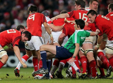 Referee Pascal Gauzere takes a tumble as Munster grind forward.