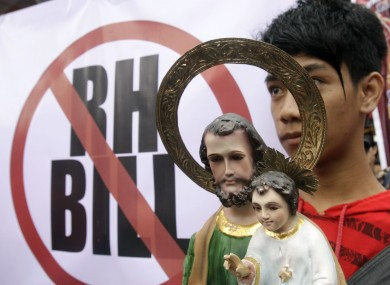 A protester carries an image of Saint Joseph with the young Jesus Christ during a rally against Reproductive Health Bill which is debated in Congress during a rally