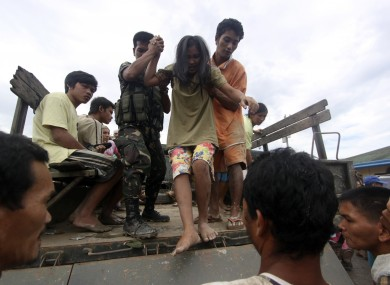 A resident who was rescued from her flooded home is assisted as she alights from a military truck in New Bataan, Compostela Valley province, southern Philippines