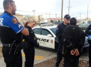 This image was provided by the Rapid City police officer Ron Terviel, left, and officer Carmen Visian, right as paramedics check a hit-and-run suspect.