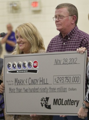 Cindy and Mark Hill hold a check for having one of two winning Powerball tickets during an announcement in Dearborn, Missouri.