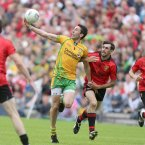 Eyes on the ball. Donegal's Rory Kavanagh concentrates on gathering possession with Aiden Branagan of Down in pursuit. (INPHO/Morgan Treacy).