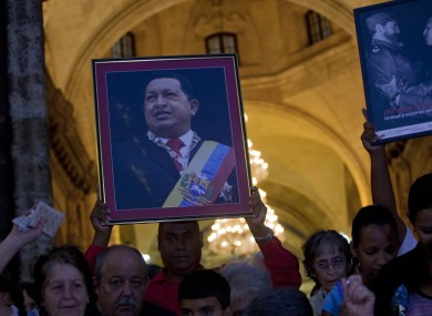 A man holds a framed image of Chavez after attending a mass to pray for the Venezuelan president's recovery