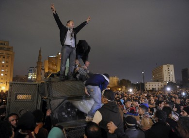 Egyptian protesters celebrate the capture of a state security armored vehicle that demonstrators commandeered during clashes