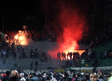 Egyptian fans rush onto the field during the deadly riot last February.