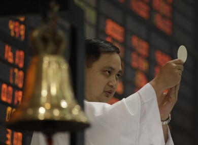 A Catholic priest makes an offertory during a mass before the start of the first day of trading at Philippine Stock Exchange.