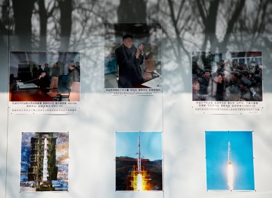 Trees are reflected on a board displaying photos of North Korean leader Kim Jong Un and the country's successful long range rocket launch outside North Korean embassy in Beijing