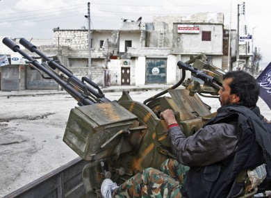 Free Syrian Army fighters sit behind their anti-aircraft weapon.